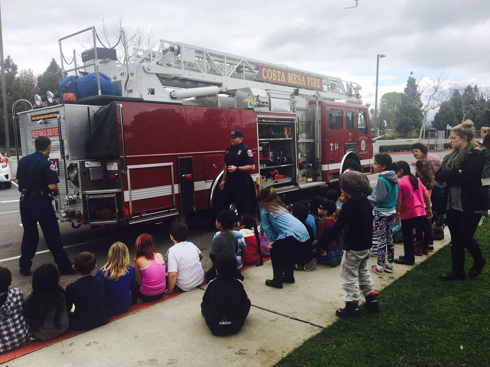 Students observe firefighters displaying their truck s features