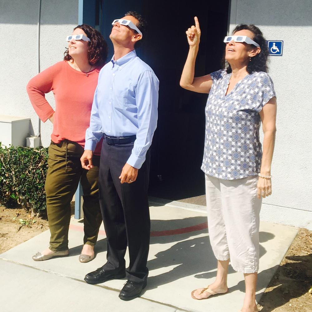 Three staff wearing solar glasses looking at the sky