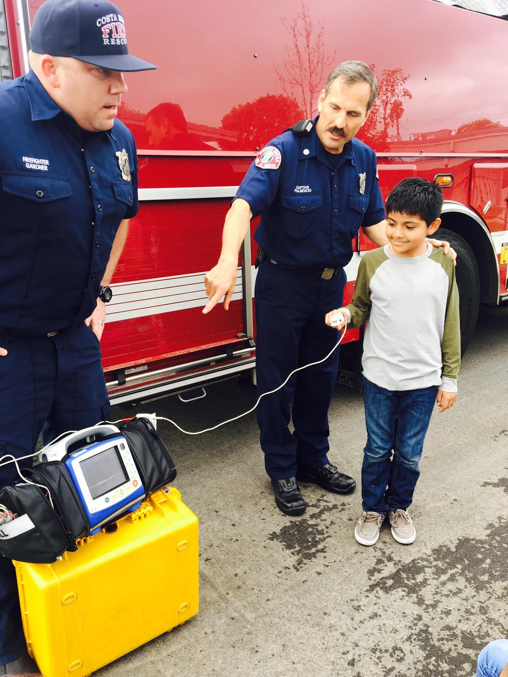 A student has his heart rate and oxygen level checked as a demonstration by the firefighters