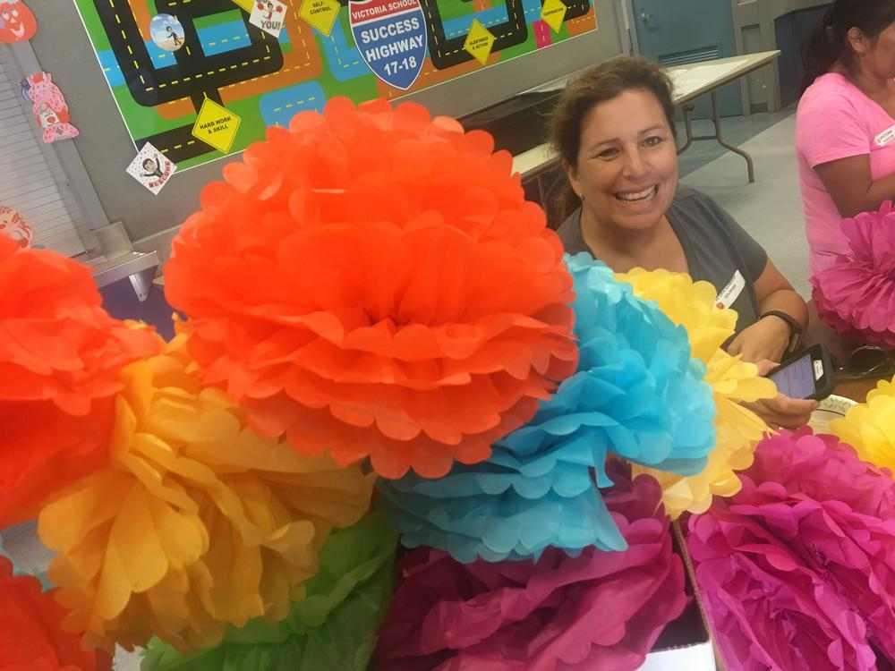 A parent at ELAC preparing decorative flowers