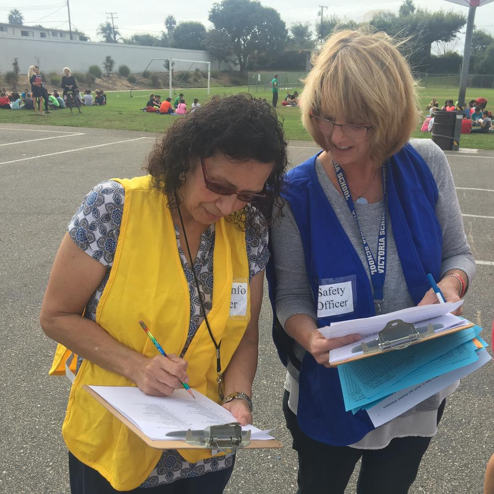 Sandee and Maria checking attendance sheets